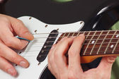 Gitarzysta umieścić palce do akordów na gitarze elektrycznej — Zdjęcie stockowe