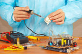 Serviceman solder electronic hardware in service workshop — Stock Photo