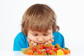 Boy with candies on white background — Stock Photo