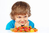 Child with candies on white background — Stock Photo