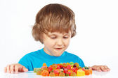 Little boy with candies on white background — Stock Photo