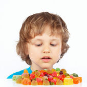 Little child with colored jelly candies on white background — Stock Photo