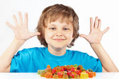 Smiling child with candies on white background — Stock Photo