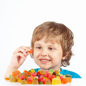 Smiling boy with jelly candies on white background — Stock Photo