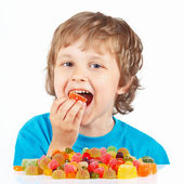 Little child eating candies on white background — Stock Photo