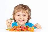 Smiling boy with candies on white background — Stock Photo