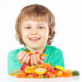 Smiling boy with sweets and candies on white background — Stock Photo