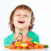 Smiling child with sweets and candies on white background — Stock Photo