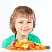 Smiling child with colored sweets and jelly candies on white background — Stock Photo