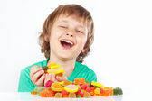 Smiling boy with sweets and jelly candies on white background — Stock Photo
