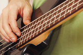 Hands of rock guitarist playing the electric bass guitar closeup — Stock Photo