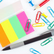 Pen, pencil, paperclips, pushpins and multicolored stickers on white desktop closeup — Stock Photo #48027313
