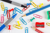 Pencil, pen, paperclips, sharpeners and pushpins on white desktop closeup — Stock Photo