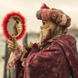 A woman with a venetian mask looking into a mirror. Venice, Italy. — Stock Photo