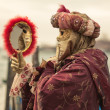 Stock Photo: Womwith venetimask looking into mirror. Venice, Italy.