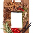 Open notebook with spices and herbs on the old wooden cutting bo — Stock Photo #12537671