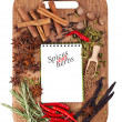 Open notebook with spices and herbs on the old wooden cutting bo — Stock Photo #12537677