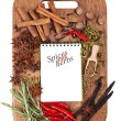 Open notebook with spices and herbs on the old wooden cutting bo — Stock Photo