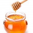 Glass jar of honey with wooden drizzler isolated on white — Stock Photo #16196265