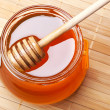 Stock Photo: Glass jar of honey with wooden drizzler