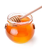 Glass jar of honey with wooden drizzler isolated on white — Stock Photo