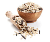 Wild brown rice in a wooden bowl isolated on white — Stock Photo