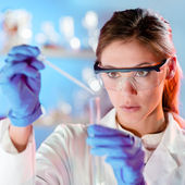 Attractive young scientist pipetting. — Stock Photo