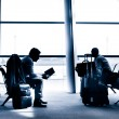 People traveling on airport silhouettes — Stock Photo #29005437