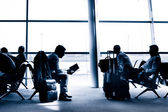 People traveling on airport silhouettes — Stock Photo
