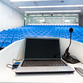 Laptop on the rostrum in conference hall. — Stock Photo