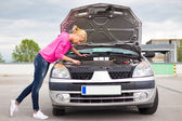 Woman inspecting broken car engine. — Stock Photo