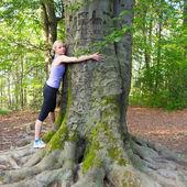 Genç kadın bir ağaca sarılmak. — Stok fotoğraf