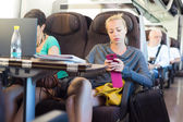 Lady traveling by train using smartphone. — Stock Photo
