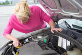 Woman inspecting broken car engine. — Stock Photo