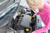 Kobieta kontroli samochód uszkodzony silnik. — Zdjęcie stockowe