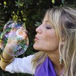 Stock Photo: Young girl blowing bubbles