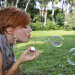 Young girl blowing bubbles — Foto Stock