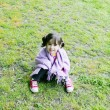 Stock Photo: Little girl sitting in grass - Family life