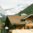 Lovely Swiss chalet with mountains in background — Stock Photo