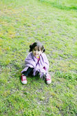 Little girl sitting in the grass - Family life — Stock Photo