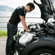 A young man fixing his car up the hills - Stock Photo