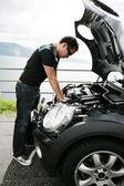 Un joven arreglando su coche las colinas — Foto de Stock
