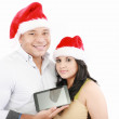 Two smiling couple holding tablet touch pad with hat santa — Stock Photo #12482136
