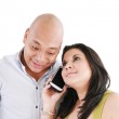Happy young couple using cell phone isolated on a white backgrou — Stock Photo #12482178