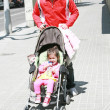 Happy father smiling with his daughter in baby carriage — Stock Photo