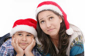 Mother and son in Santa hats smiling and looking up — Stock Photo