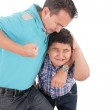 Young boy being aggressively held up by his father — Stock Photo #13438935