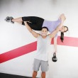 Handsome man lifting a beautiful woman at the gym — Stock Photo #13615134