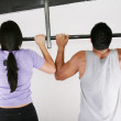 Young adult fitness woman and man preparing to do pull ups in pu — Stock Photo #13615215