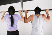 Young adult fitness woman and man preparing to do pull ups in pu — Stock Photo